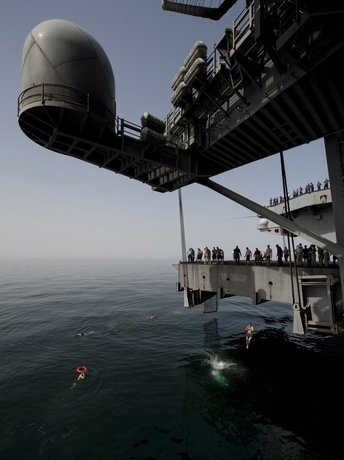 sailors-during-a-swim-call-jump-off-an-aircraft-elevator-aboard-the-nimitz-class-aircraft-carrier-uss-carl-vinson-into-the-arabian-sea.jpg